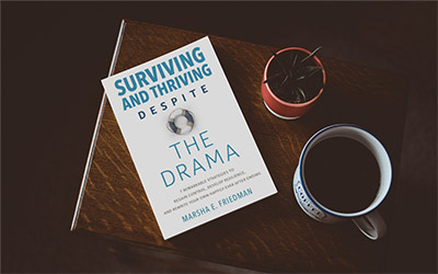 Marsha Friedman's book Surviving and Thriving Despite the Drama on a coffee table