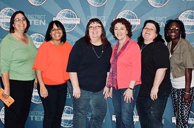 Marsha and a group of women in front of Toastmasters International Logo